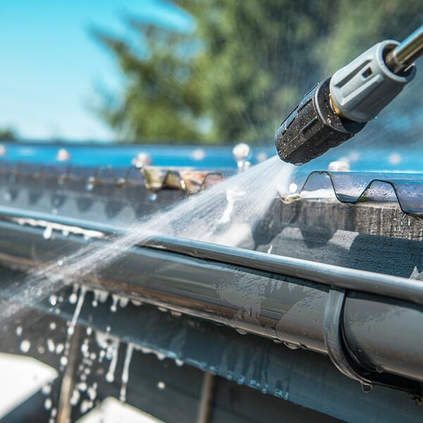spring rain gutters cleaning using pressure washer