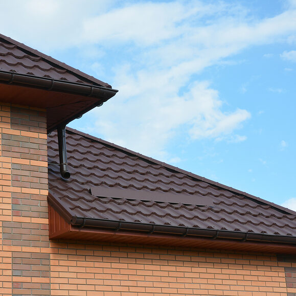 house metal roof corner with rain gutter pipeline.